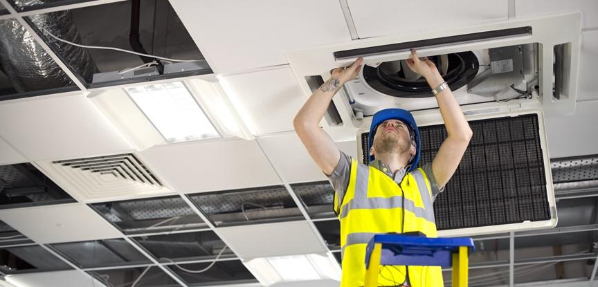 foto de homem mexendo no sistema de ar condicionado
