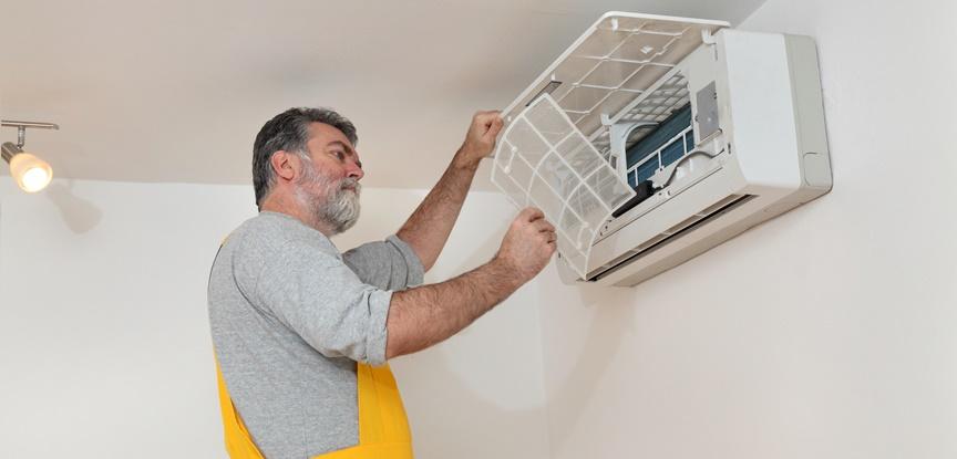 foto de homem mexendo no ar condicionado