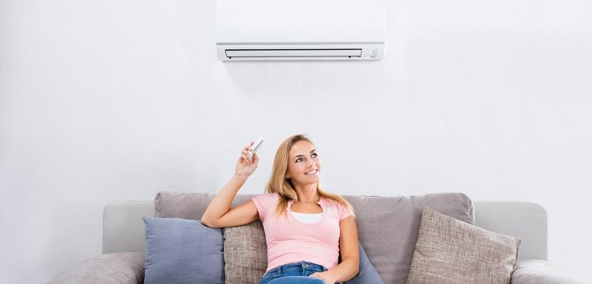 foto de mulher sentada no sofá ligando ar condicionado
